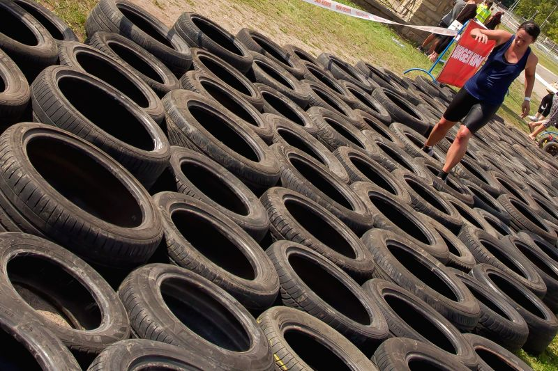 A competitor runs through an obstacle of tyres during an extreme obstacle race in Ferenc Puskas stadium in Budapest, Hungary on Aug. 30, 2014. About 1,700 ...