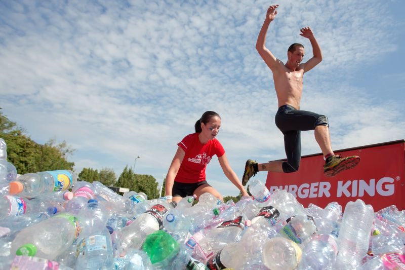 Competitors jumps through an obstacle of plastic bottles during an extreme obstacle race in Ferenc Puskas stadium in Budapest, Hungary on Aug. 30, 2014. About ...