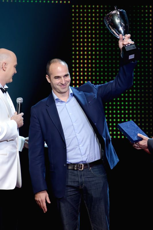 Tibor Benedek, coach of the Hungarian men's water polo team, poses with the trophy for the head coach of the year 2013 in Budapest Dec. 19, 2013. ...