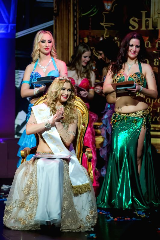 Winner Szilvia Vago (C) with runner-ups Roberta Toth (L) and Gyongyi Stuber (R) celebrate their victory in the Miss Bellydance Hungary 2014 competition in Budapest, Hungary, on Dec. 7, ...