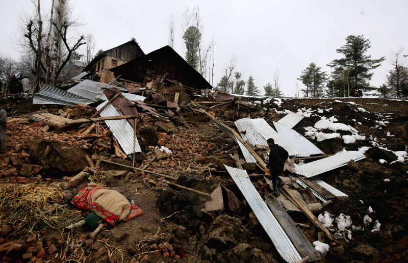 A view of the houses damaged in a landslide at Charari Sharief in Jammu and Kashmir`s Budgam district on March 30, 2015. Sixteen people were buried alive as two houses collapsed and a young ...