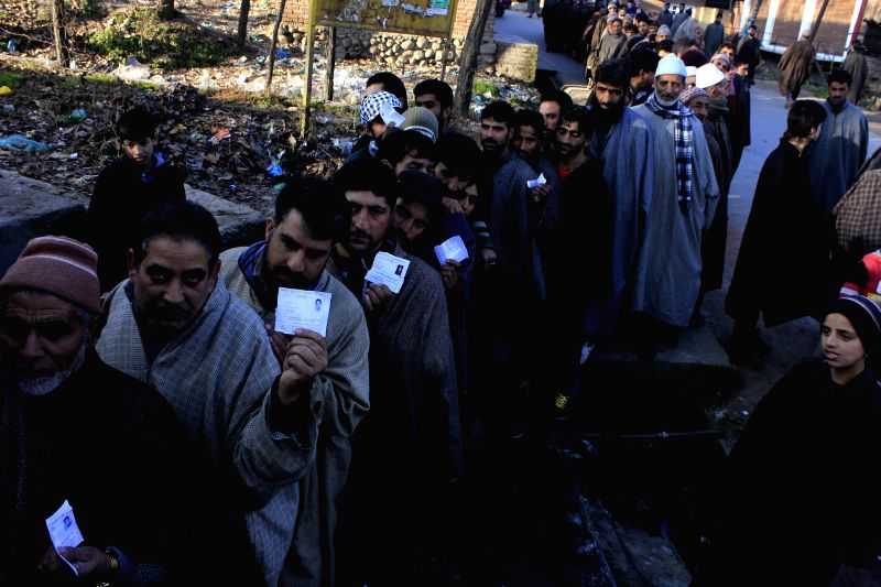People queue-up to cast their votes during the third phase of Jammu and Kashmir assembly polls at Kramshore Village in Khansahib constituency of Budgam district on Dec 9, 2014.