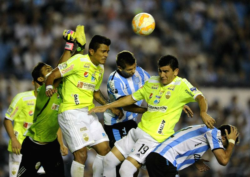 Racing Club's Leandro Grimi (C) of Argentina, vies for the ball with Deportivo Tachira's Carlos Javier Lopez (2-R) of Venezuela, during the match of Copa ...