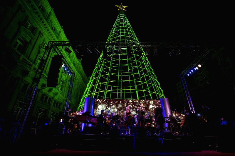 Buenos Aires: Artists perform carols in front of the Christmas Tree at Estado del Vaticano Square, in Buenos Aires City, Argentina, on Dec. 7, 2014. The 40m-high Christmas Tree, has HD LED screens, ..