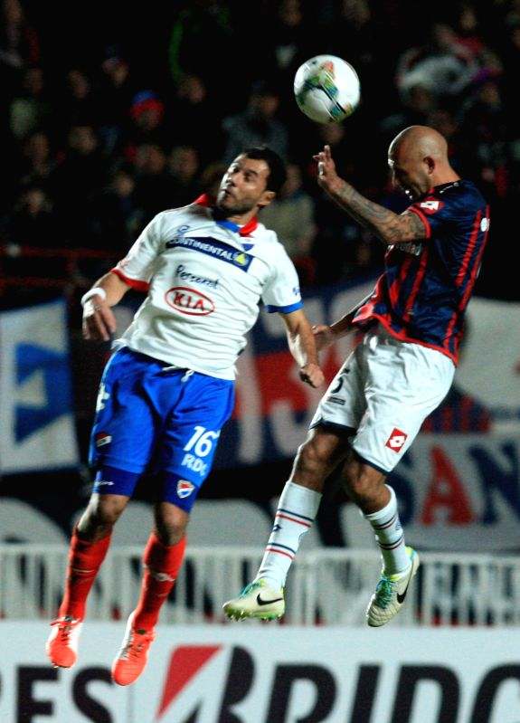 Juan Mercier (R) of San Lorenzo vies for the ball with Nacional's Fredy Bareiro (L), during their second leg final match of the 2014 Libertadores Cup, held at .