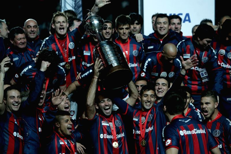 Players of San Lorenzo celebrate their victory with the trophy, after the second leg final match of the 2014 Libertadores Cup against Nacional, held at Pedro ..