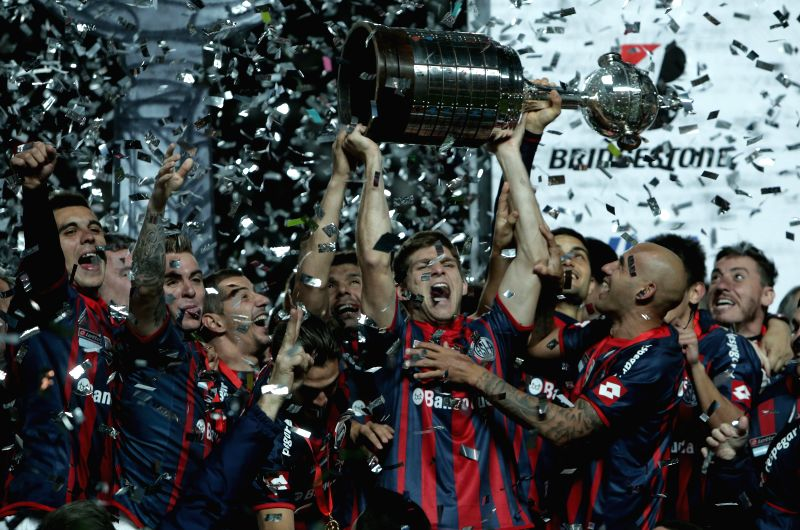 Players of San Lorenzo celebrate their victory with the trophy after the second leg final match of the 2014 Libertadores Cup against Nacional, held at Pedro ...