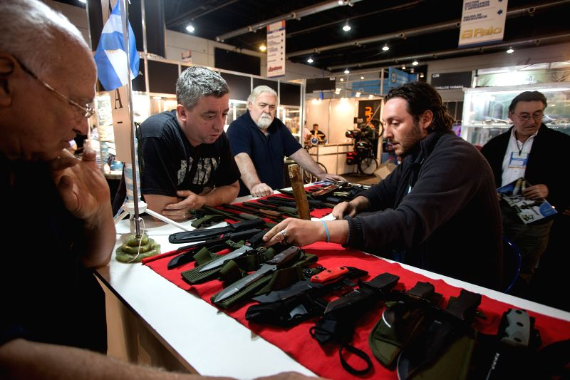 A salesman shows military and hunting knives to visitors during the 23rd International Hunting, Fishing and Outdoors Fair, in the La Rural fairgrounds, in ...