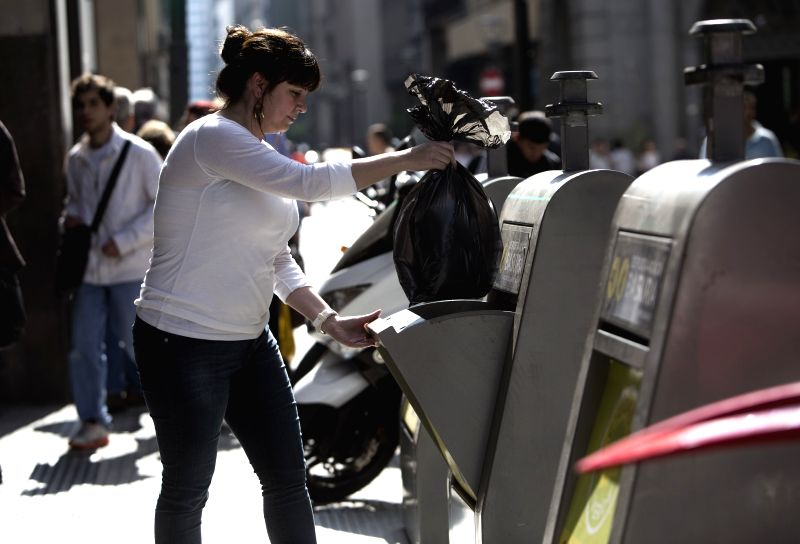 A woman throws a wastes bag in a underground waste container in Buenos Aires city, Argentina, on Aug. 22, 2014. Buenos Aires city launched the new underground .