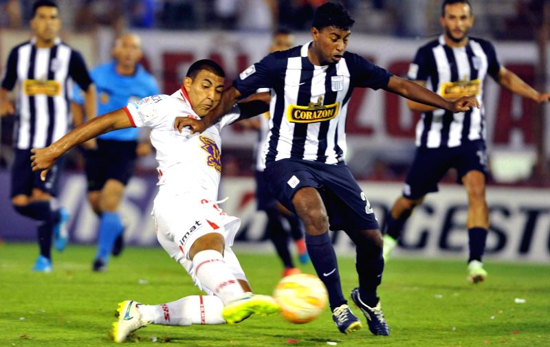 Huracan's Ramon Abila (L) of Argentina vies with Alianza Lima's Miguel Araujo (R) of Peru during the match of Copa Libertadores in Buenos Aires, Argentina, on .