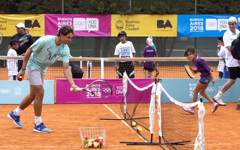 Spanish tennis player Rafael Nadal (L) plays tennis with a girl during a tennis clinic in Buenos Aires, Argentina, Feb. 26, 2015.