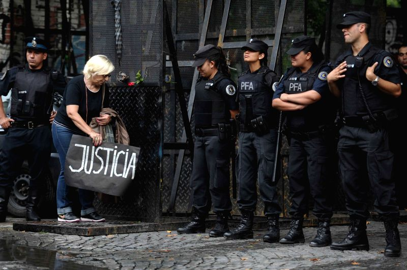 A woman holds banners in front of the police during the wake ceremony of the late prosecutor Alberto Nisman in Buenos Aires, Argentina, on Jan. 28, 2015. ...