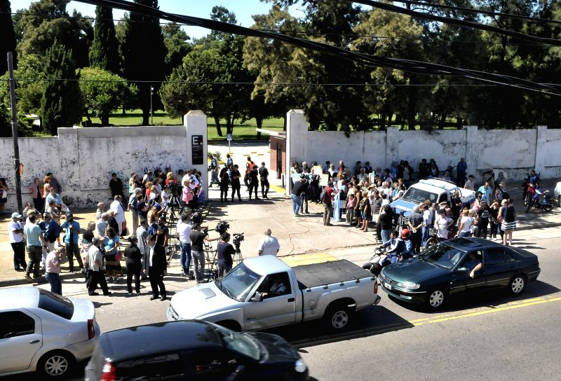People wait for the arrival of the funeral procession of late prosecutor Alberto Nisman in front of La Tablada cementery in Buenos Aires, Argentina, on Jan. ...
