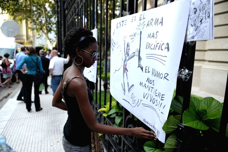 A woman places a banner during a demonstration for the victims of the shooting in the offices of the French journal Charlie Hebdo in Paris, in front of the ...