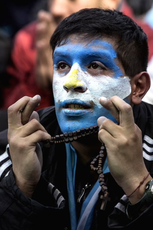 An Argentina's fan reacts while watching the broadcast of a Group F match between Argentina and Nigeria of 2014 FIFA World Cup on a screen installed in San ...