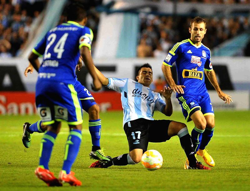 Racing Club's Marcos Acuna (C) of Argentina vies for the ball with Sporting Cristal's Horacio Calcaterra (R) of Peru at the match of Copa Libertadores in the ...