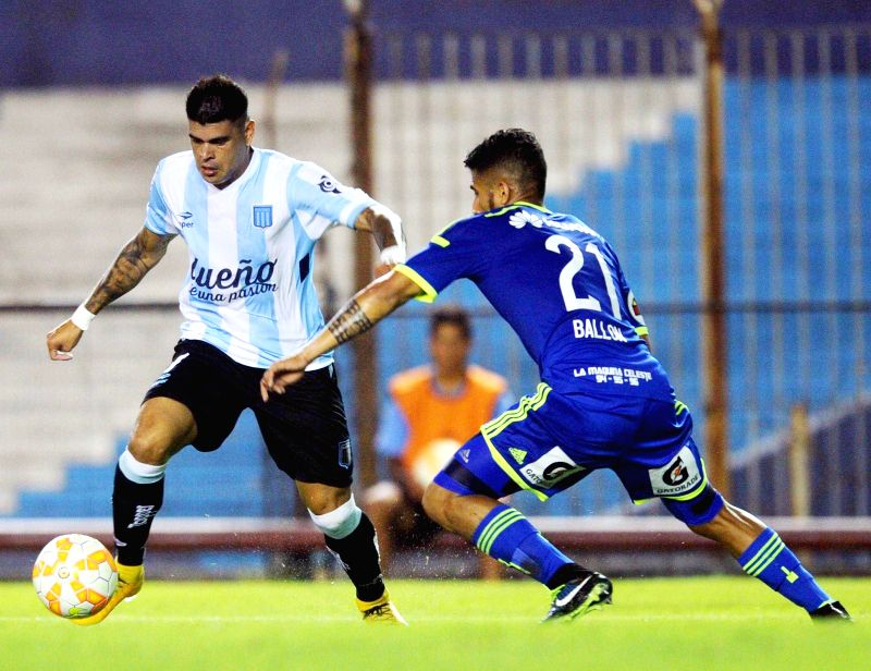 Racing Club's Gustavo Bou (L) of Argentina vies for the ball with Sporting Cristal's Josepmir Ballon of Peru during the match of Copa Libertadores in the ...