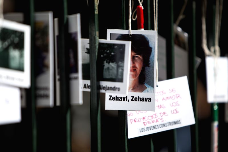 Images of the victims are placed at a memorial during the commemoration event of the 23rd anniversary of the attack against Israel's embassy in Buenos Aires ...