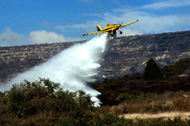 An aircraft splashes water on the area of the forest fire in the Sierra de los Padres, in the province of Buenos Aires, Argentina, on March 19, 2015. About ...