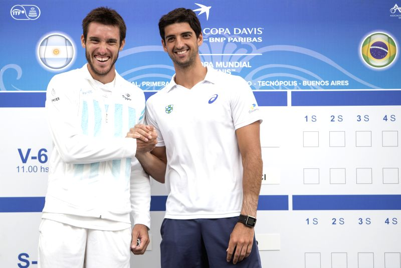 Argentina's tennis player Leonardo Mayer (L) greets Brazilian player Thomaz Bellucci during the official draw of their upcoming Davis Cup tennis match at ...