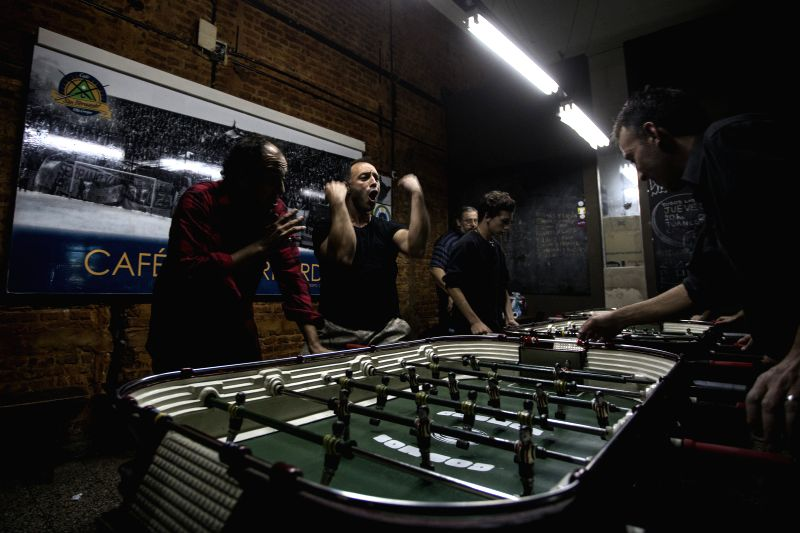 Image taken on May 8, 2014 shows residents reacting during a table football's championship in a bar in Buenos Aires, Argentina. In Argentina, the game of the ...