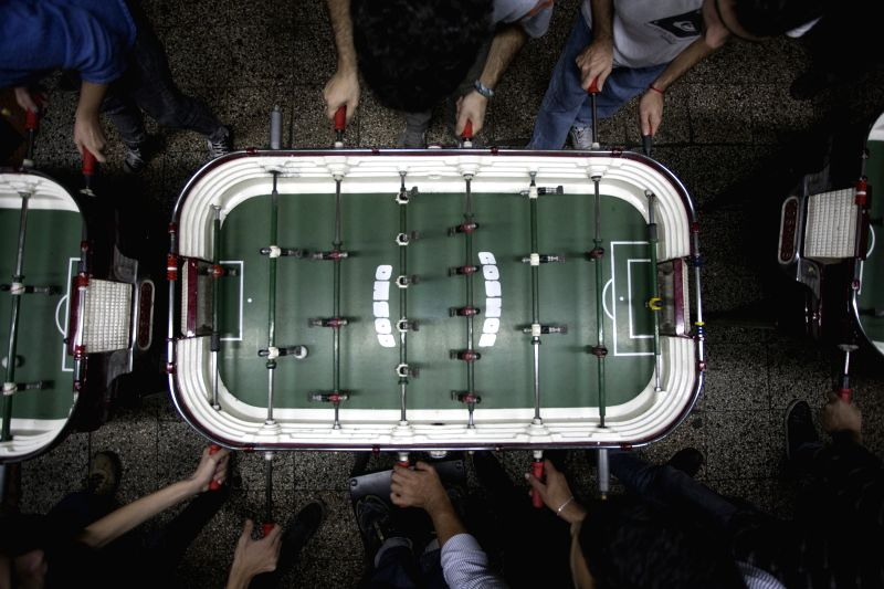 Image taken on May 8, 2014 shows residents playing during a table football's championship in a bar in Buenos Aires, Argentina. In Argentina, the game of the ...