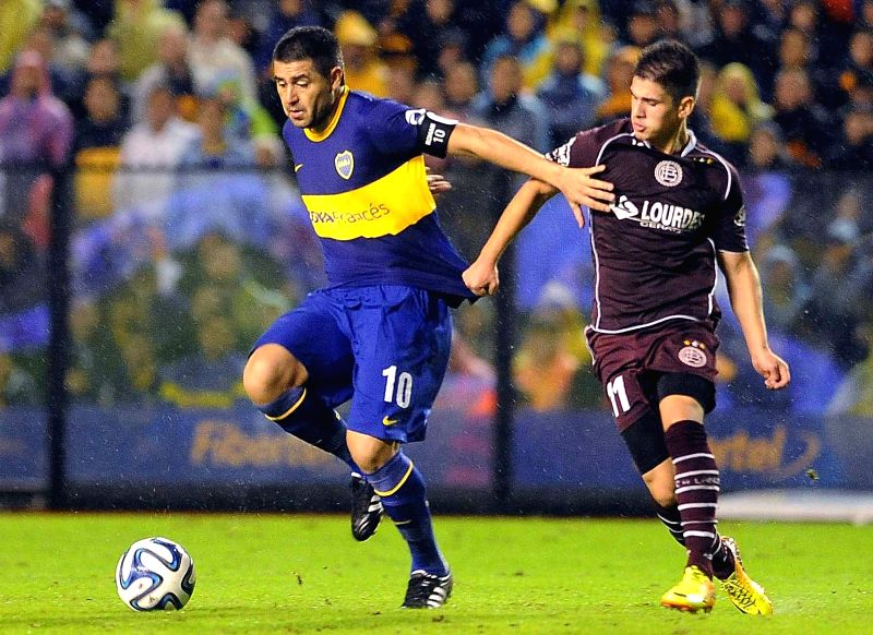 Juan Roman Riquelme (L) of Boca Juniors vies with Jorge Valdez of Lanus during the match of the Final Tournament 2014, in the Alberto J. Armando Stadium in ...