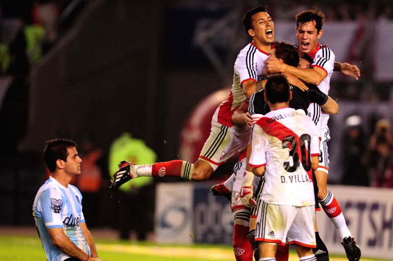 Goalkeeper Leandro Chichizola (in black) of River Plate celebrates with his teammates in front of Valentin Viola (L) of Racing Club during the match of the Final