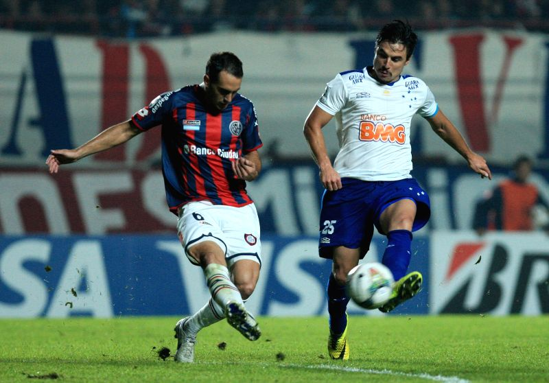 San Lorenzo's Santiago Gentiletti (L) vies for the ball with Cruzeiro's William (R), during their first leg quarterfinal match of the 2014 Libertadores Cup at ...