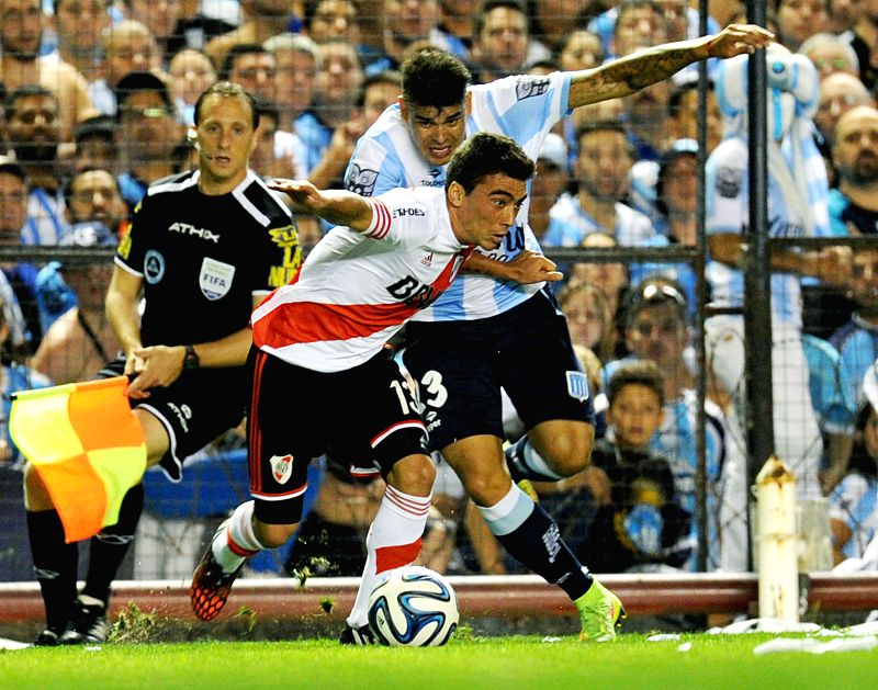 Buenos Aires: Racing's Gustavo Bou (R) vies with Bruno Uribarri (C) of River Plate during a match, in Buenos Aires, Argentina, on Nov. 23, 2014.