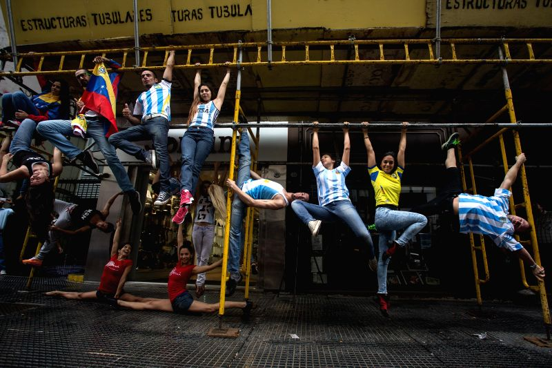 Buenos Ares: Competitors of the Argentina and South America Pole Championship 2014 show their pole dance skills on scaffoldings in a street in Buenos Ares, Argentina, on Nov. 21, 2014. Around 100 ...
