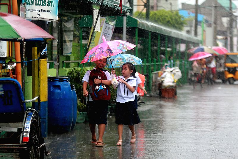 BULACAN, July 20, 2018 - Students share an umbrella in heavy rain brought by tropical storm Ampil in Bulacan Province, the Philippines, July 20, 2018.