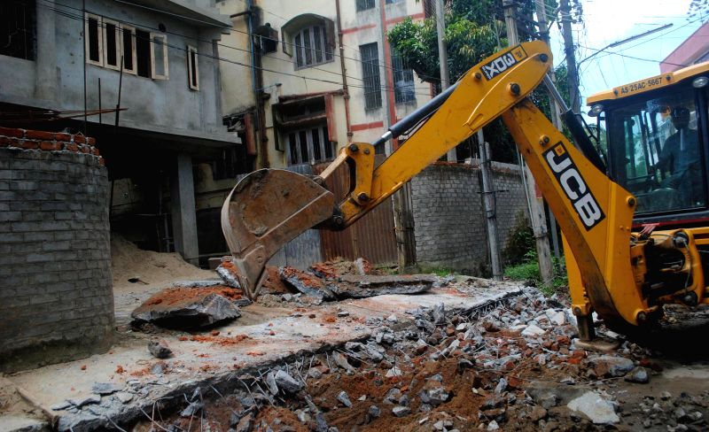 Bulldozers demolish  alleged illegal structures in Guwahati on Aug 6, 2014.