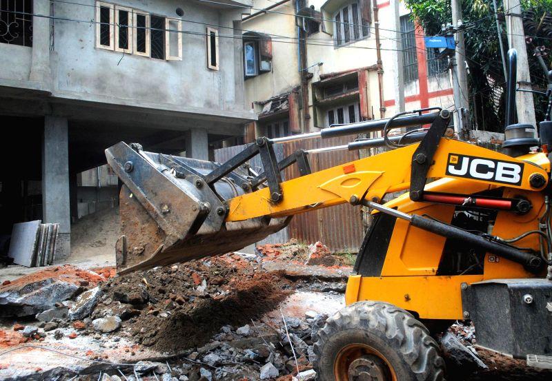 Bulldozers demolish  alleged illegal structures in Guwahati on Aug 6, 2014.