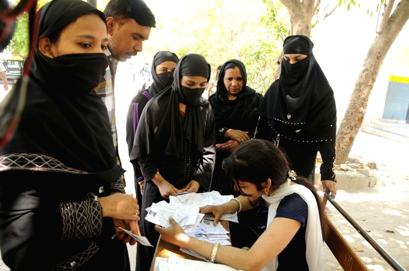 Burqa clad women at a polling booth during the third phase of 2014 Lok Sabha Polls in New Delhi on April 10, 2014. Elections are being held in 91 parliamentary constituencies of India.