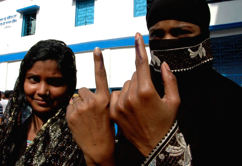 Burqa clad women show their fore fingers marked with phosphorous ink after casting their votes at a polling booth during the seventh phase of 2014 Lok Sabha Polls in Howrah of West Bengal on April ...