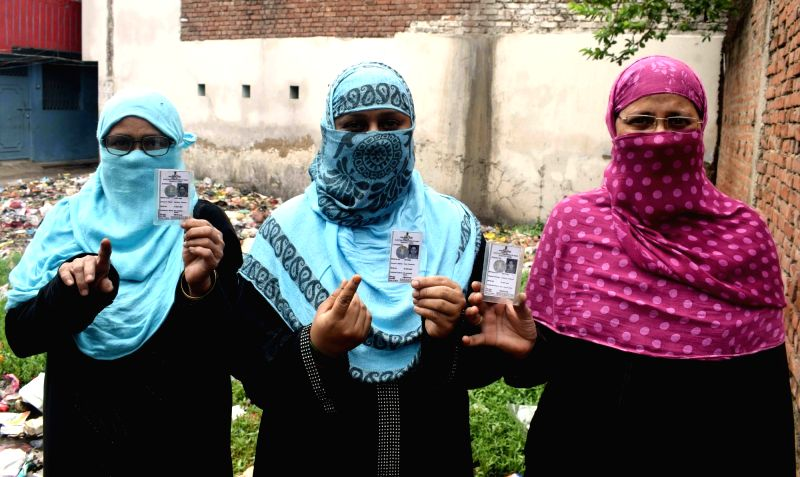 Burqa clad women, shows their forefingers marked with phosphorous ink after casting vote during Patna Municipal Corporation elections on June 7, 2017.