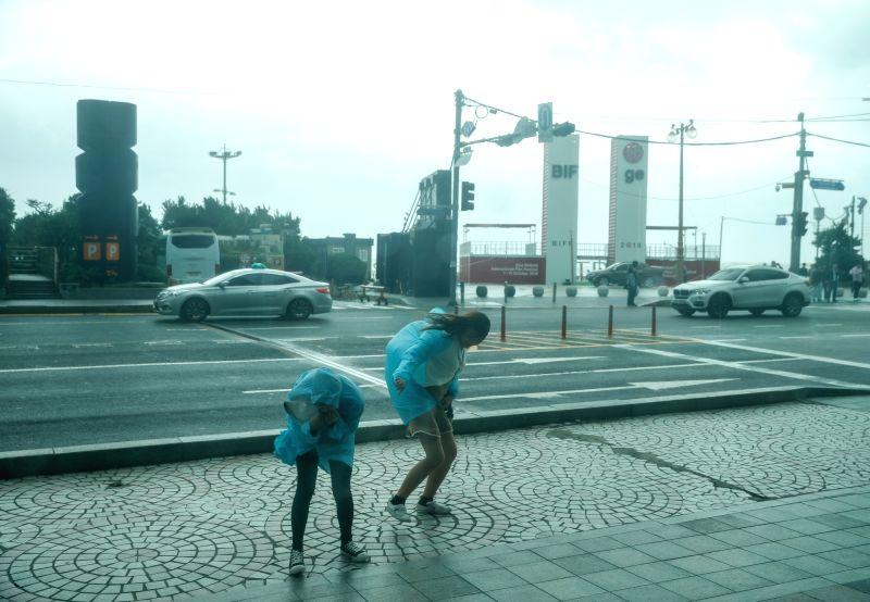 BUSAN, Oct. 6, 2018 (Xinhua) -- People walk against strong wind near the Haeundae Beach in Busan, South Korea, on Oct. 6, 2018. Typhoon Kong-rey landed in South Korea Saturday, bringing strong wind and heavy rain. (Xinhua/Wang Jingqiang/IANS)