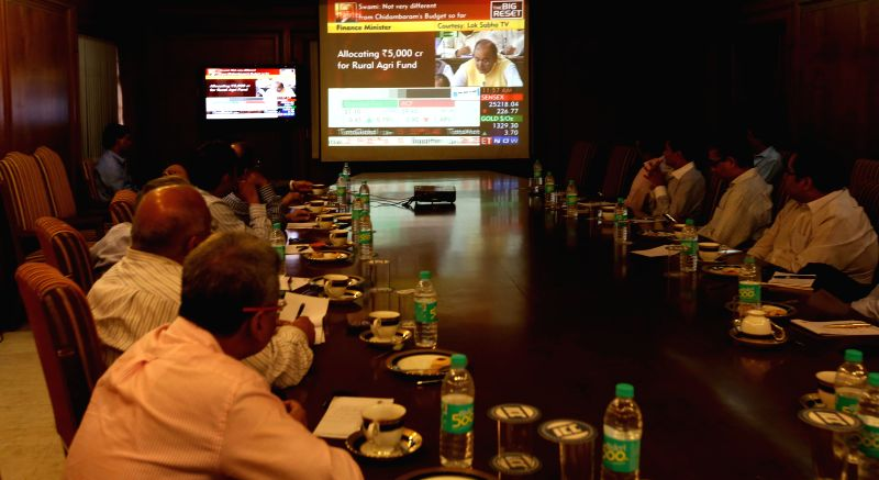 Businessmen closely follow Union Finance Minister Arun Jaitley's General Budget speech for 2014-15 at Indian Chamber of Commerce in Kolkata on July 10, 2014.