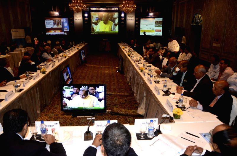 Businessmen closely follow Union Finance Minister Arun Jaitley's General Budget speech for 2014-15 in Mumbai on July 10, 2014. - Arun Jaitley