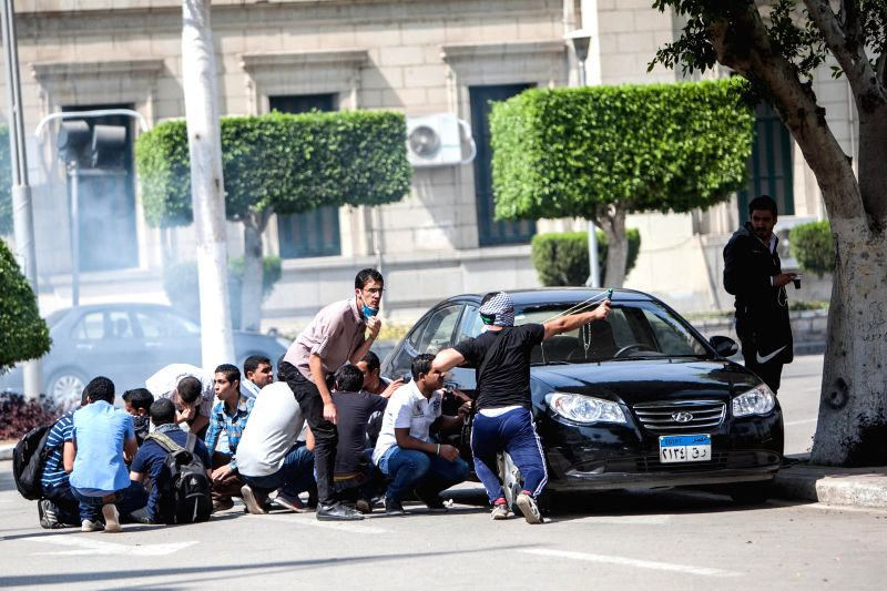 Anti-military students take cover during a clash with riot police at the Cairo University campus in Cairo, Egypt, April 14, 2014. At least one person was killed and .