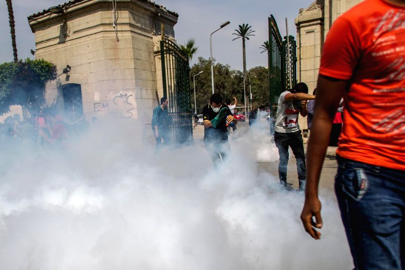 Anti-military students run away from tear gas during a clash with riot police at the Cairo University campus in Cairo, Egypt, April 14, 2014. At least one person was