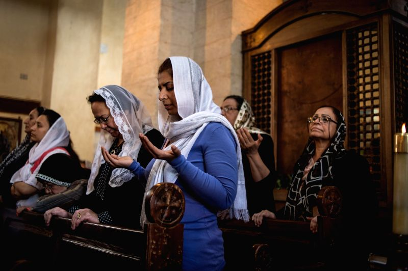 Egyptian Coptic women attend a mass on Holy Thursday at a church in Cairo, Egypt, on April 17, 2014. The Copts are the native Christians of Egypt. Holy Week in ...