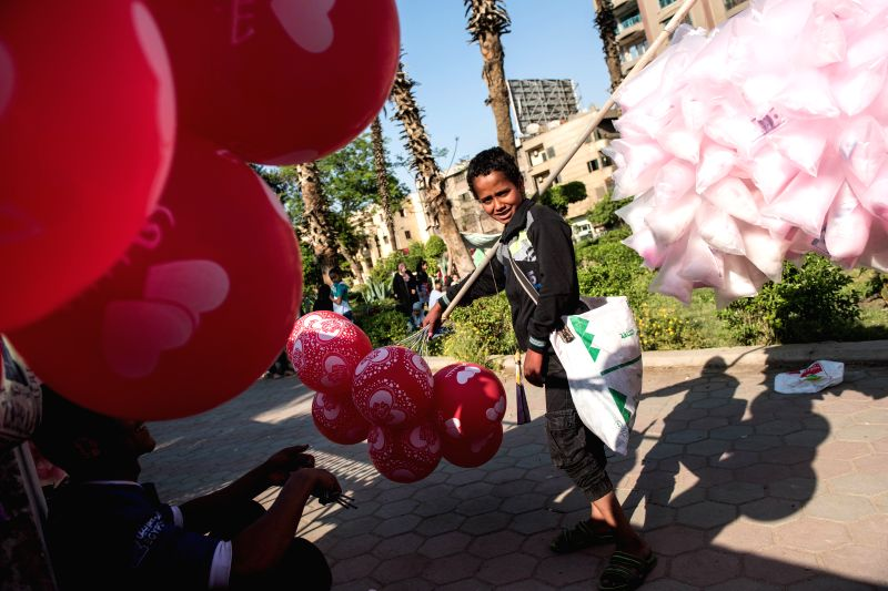 "CAIRO, April 18, 2017 - A vendor sells balloons and candies during the traditional Egyptian festival ""Sham el-Nessim"" along the bank of Nile River in Cairo, Egypt, April 17, 2017. Falling ..."