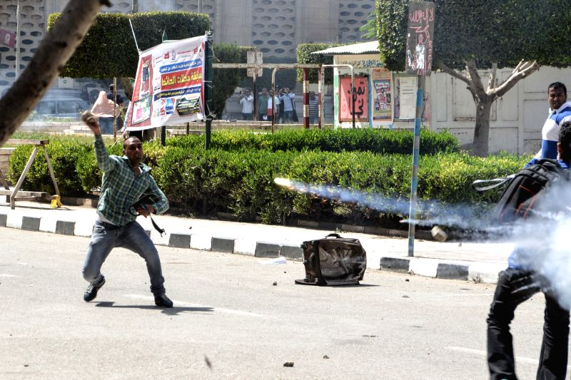Students of Cairo University are seen in clashes with security personnel after a demonstration was stopped on campus in Cairo, Egypt, on April 19, 2015. ...