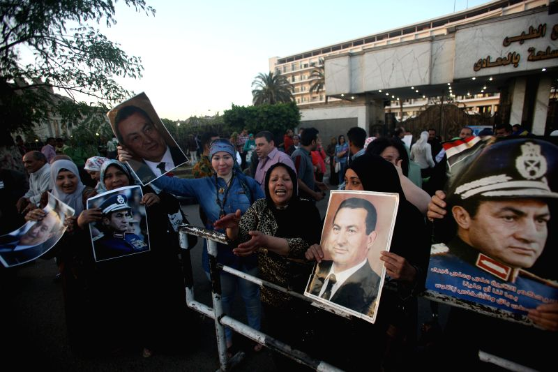 Supporters of former Egyptian President Hosni Mubarak hold posters of his portrait as a way of celebration for the 33rd Sinai Liberation Day in front of Maadi ...