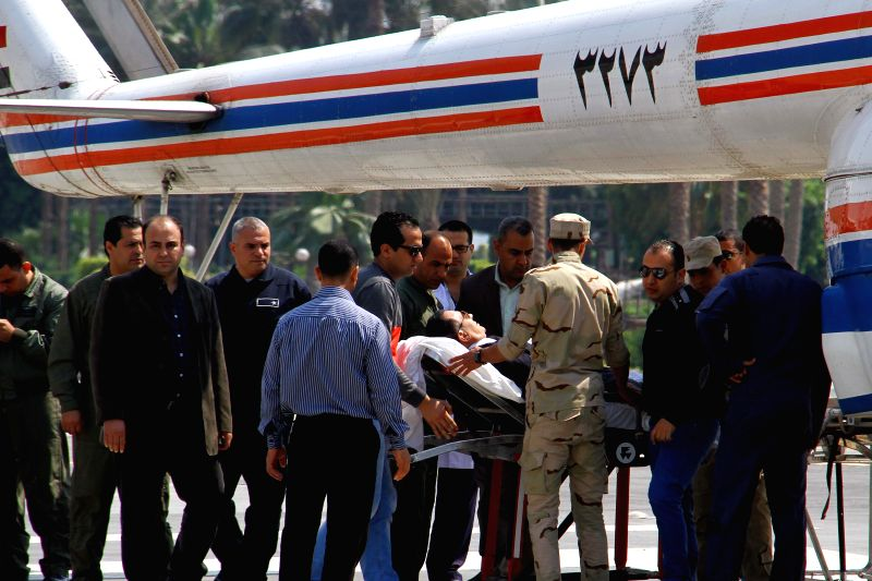 Egypt's former President Hosni Mubarak (C) is carried down from a helicopter arriving at the Maadi Armed Forces Hospital where he is house arrested, after his retrial ...