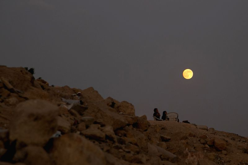 "An Egyptian couple sits on top of a hill when the ""Supermoon"" rises in Cairo, Egypt, on Aug. 10, 2014. The ""supermoon,"" technically known as ..."