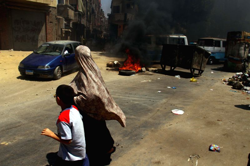 An Egyptian woman and a boy walk past a fire set by supporters of Egypt's ousted president Mohamed Morsi during a demonstration in east Cairo, Egypt, Aug. 14, 2014. ..