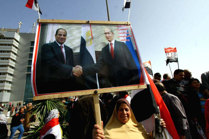 Egyptians hold banners and posters as they wait for the arrival of Russian President Vladimir Putin at the Cairo International Airport in Cairo, Egypt, on Feb. 9, ...
